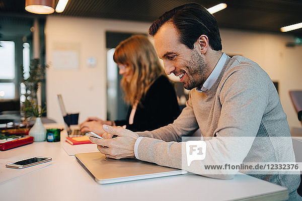 Side view of smiling businessman using smart phone while sitting by businesswoman at desk in creative office