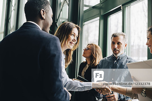 Mature businesswoman greeting colleagues in meeting at office