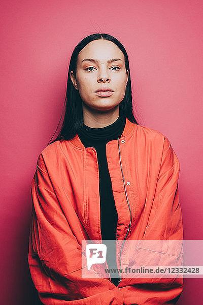 Portrait of confident woman wearing orange jacket over pink background