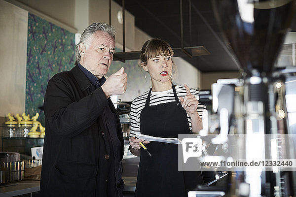 Female barista and owner gesturing while discussing in cafe