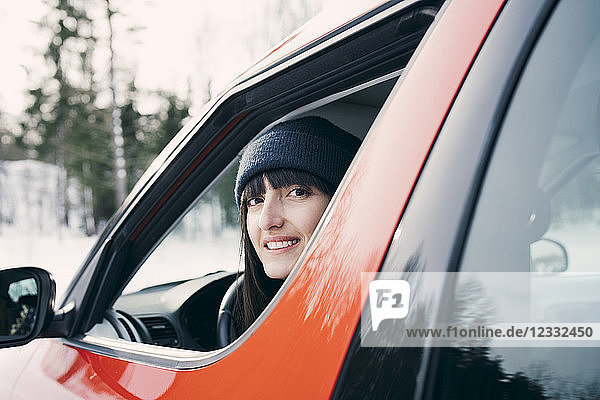 Portrait of smiling woman sitting in red car