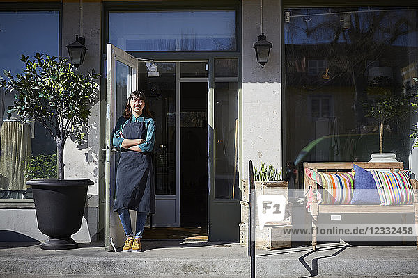 Full length portrait of female owner standing by doorway at store