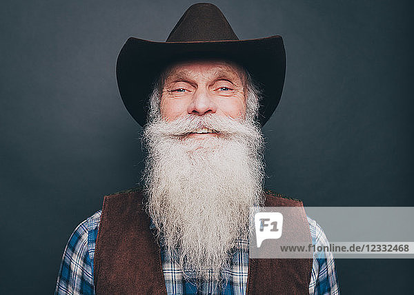 Portrait of happy bearded senior man wearing cowboy hat on gray background