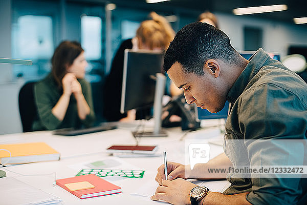 Side view of confident businessman writing on paper while female colleagues working at creative office