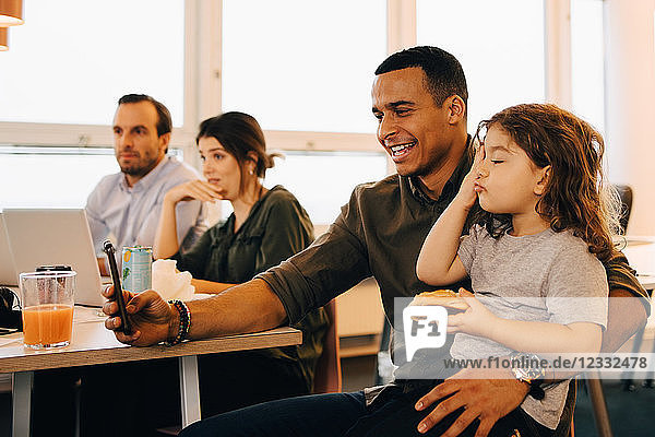 Smiling businessman taking selfie with son while sitting by colleagues at creative office