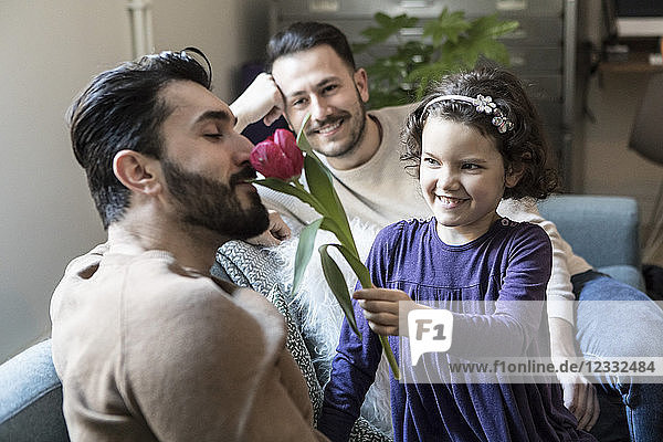 Smiling daughter making father smell tulip while sitting with man on sofa in living room