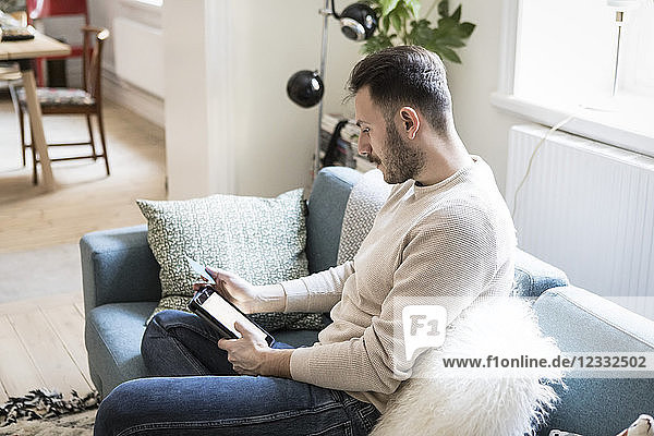 Young man doing online shopping on digital tablet through credit card while sitting on sofa at home