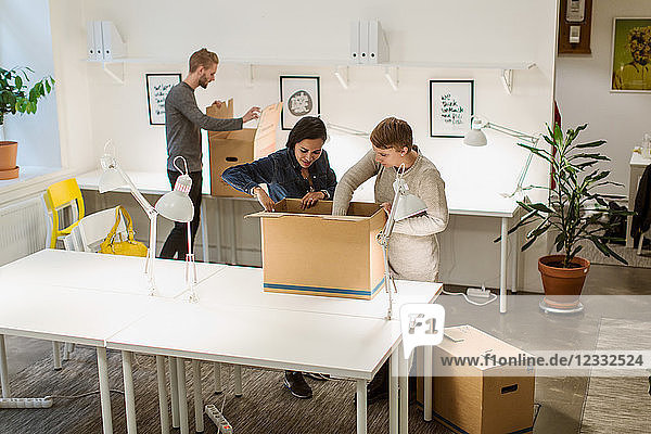 High angle view of multi-ethnic business coworkers opening cardboard boxes at creative office