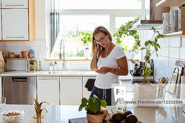 Woman listening music through mobile phone while standing in kitchen