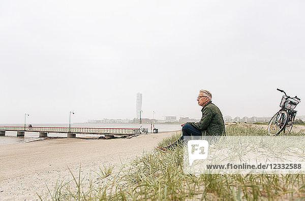 Full length of senior male commuter sitting on sand at beach against clear sky