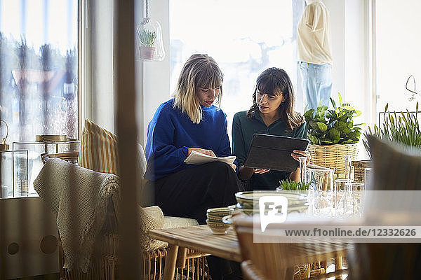 Female owners discussing over digital tablet at boutique