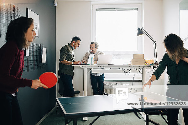 Female professionals playing table tennis while male colleagues using laptop at creative office