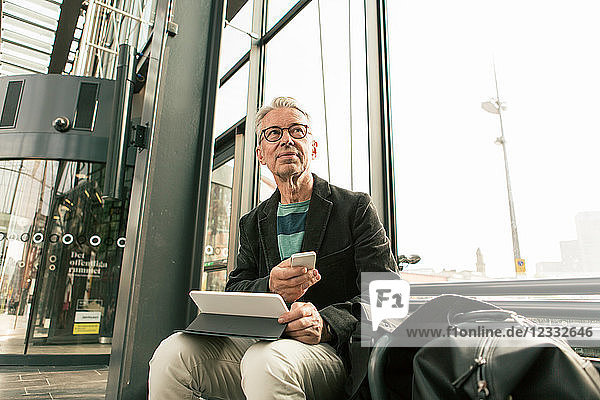 Low angle view of senior male commuter looking away sitting with technologies by bags at railroad station