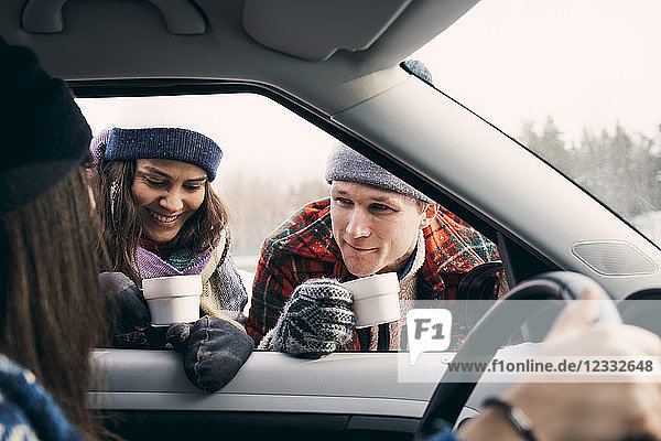 Smiling man and woman talking to friend sitting in car while having coffee during winter