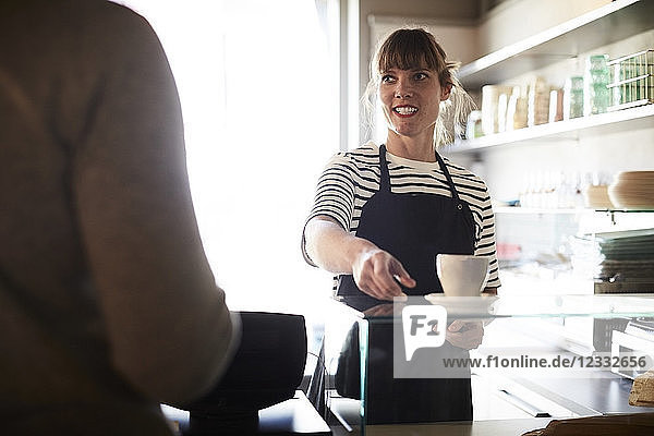 Smiling female barista serving coffee to male customer at cafe