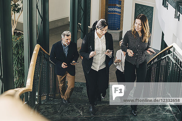 Full length of business people walking on steps in office