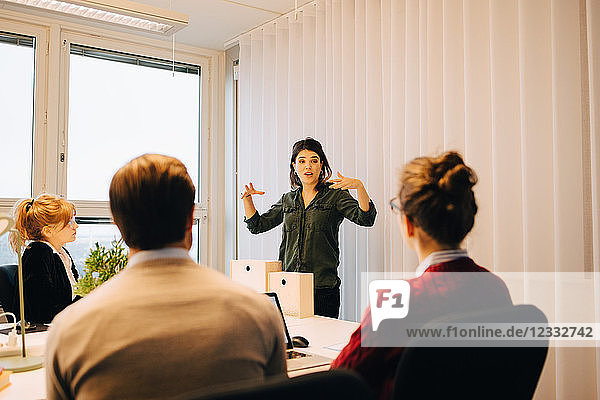 Confident businesswoman explaining strategy to colleagues sitting in board room at creative office