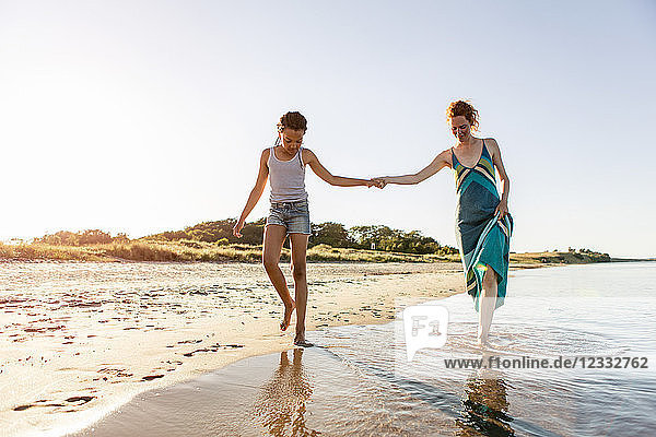 Full length of mother and daughter holding hands while walking on shore at beach against clear sky