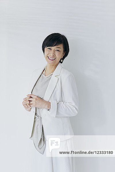 Japanese senior businesswoman against white wall