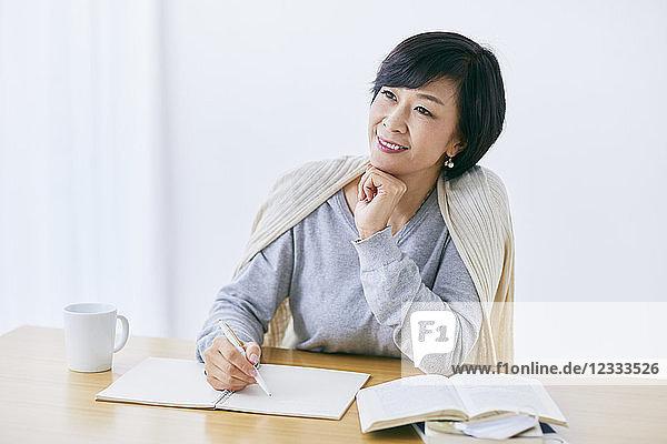 Japanese senior woman working at table