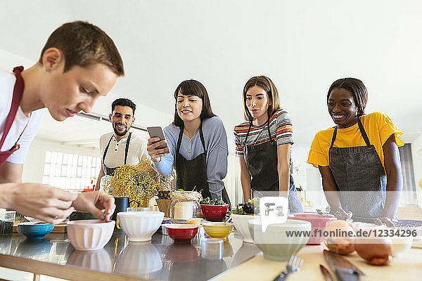 Friends in a cooking workshop watching instructor