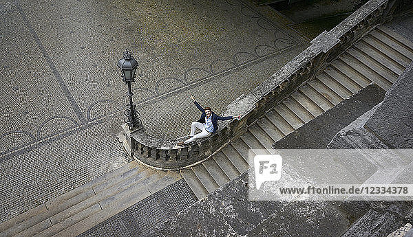 Germany  Munich  Businessman with raised arms siting on banister