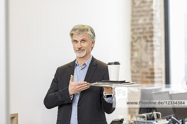 Confident businessman presenting mobile devices with cup of coffee on top