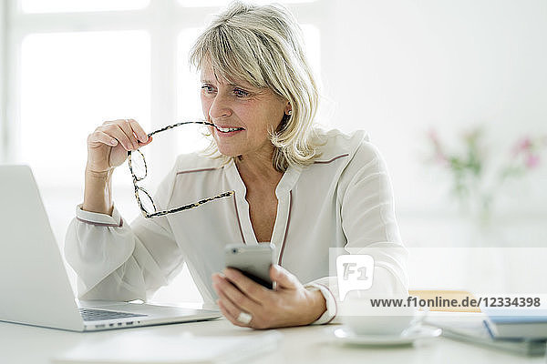 Mature businesswoman holding cell phone working on laptop at desk