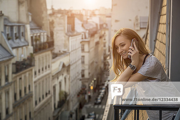 France  Paris  portrait of smiling woman on the phone standing on balcony in the evening