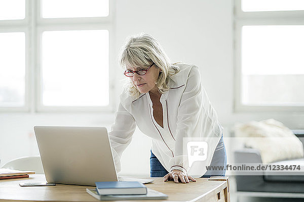 Mature businesswoman working on laptop at desk