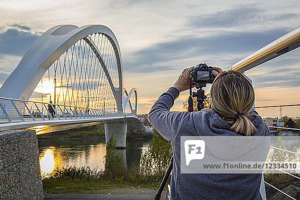 France,  Alsace,  Strasbourg,  Passerelle des Deux Rives at sunset,  female photographer in the foreground