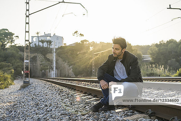 Young man sitting on railroad track