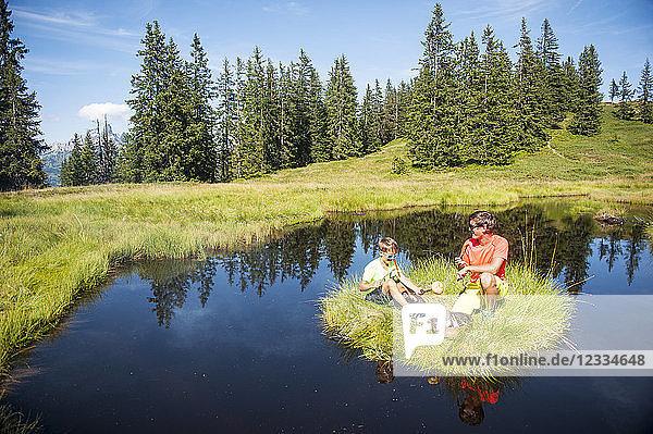 Austria  Salzburg State  Untertauern  father and son grilling on small island