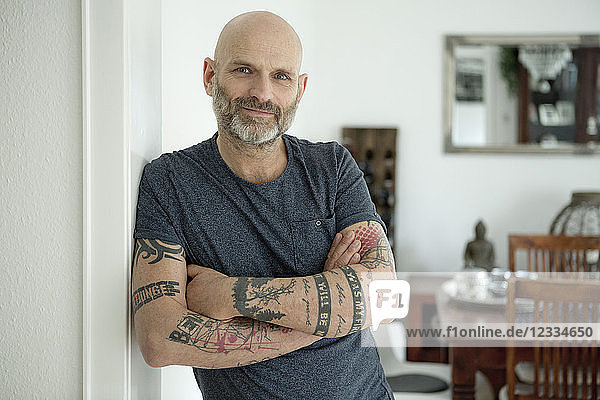 Tattooed man leaning in door of his home  with arms crossed