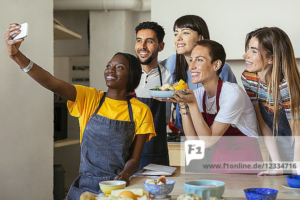 Friends and instructor in a cooking workshop taking a selfie