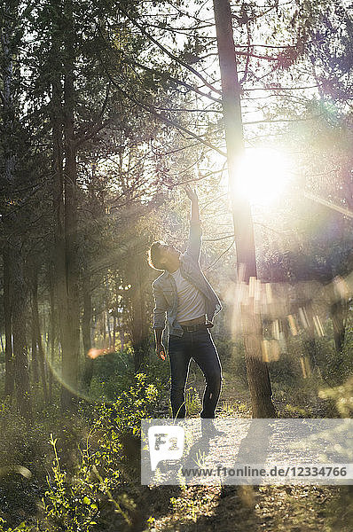 Young man standing in forest  against the sun