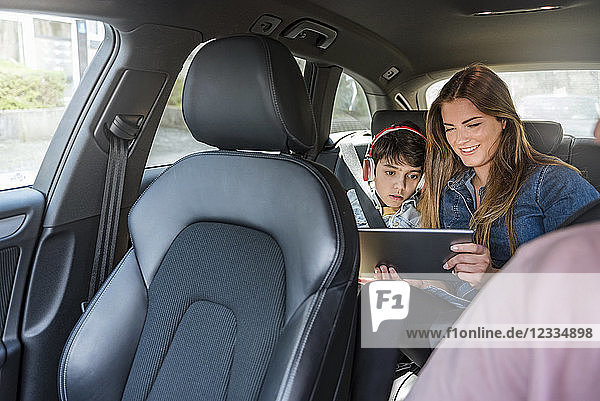 Family on a road trip with mother and son sharing tablet