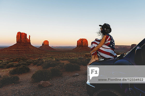 USA,  Utah,  Woman with United States of America flag enjoying the sunset in Monument Valley