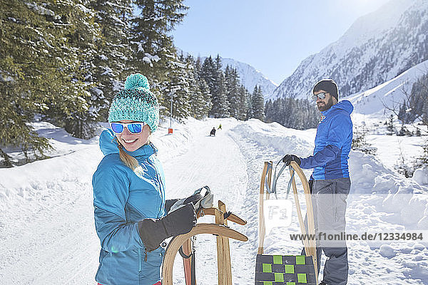 Couple with sledges standing in snow-covered landscape