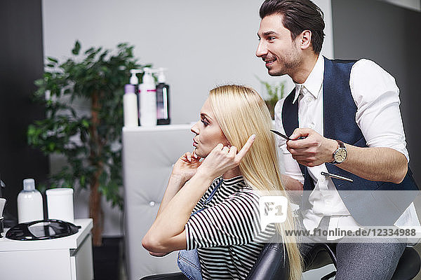 Woman talking to hairdresser in hair salon