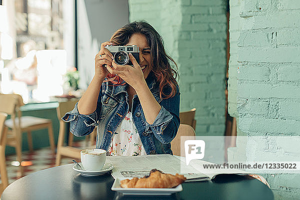 Laughing woman sitting in coffee shop taking pictures with camera