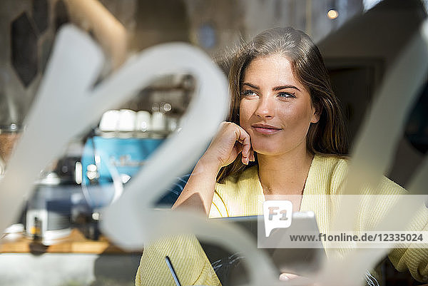 Smiling young woman with tablet in a cafe