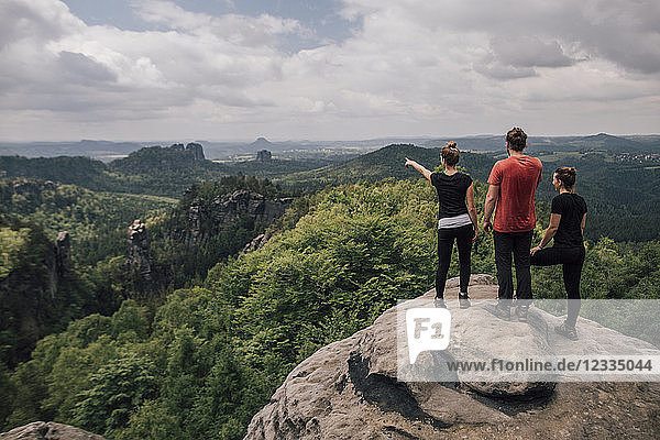Germany  Saxony  Elbe Sandstone Mountains  friends on a hiking trip standing on rock
