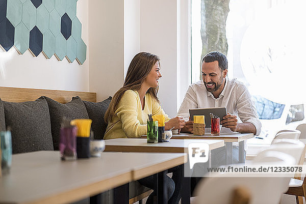 Young woman and happy man with tablet in a cafe