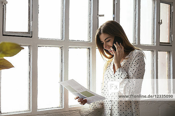 Happy young woman on cell phone looking at document at the window