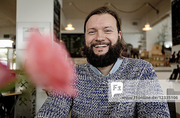 Man with beard sitting in cafe,  portrait