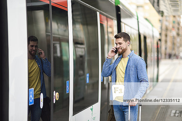Young man with smartphone in front of tram