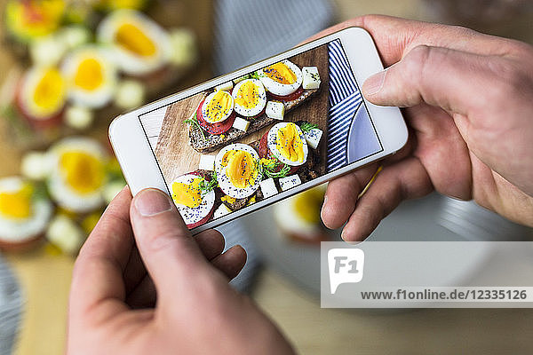 Man holding smartphone with photo of vegetarian breakfast with bread and eggs