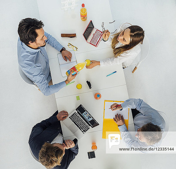 Four business people at meeting table in office  top view