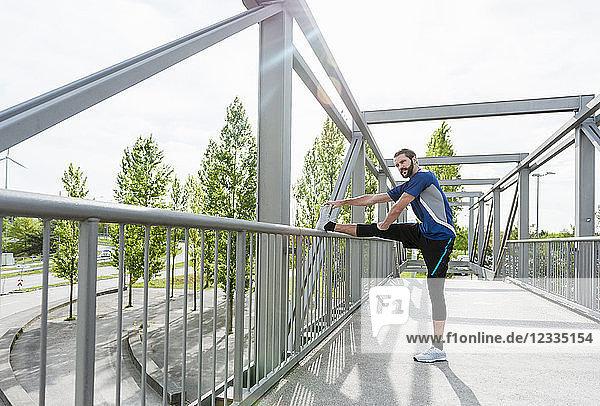 Man stetching on a bridge
